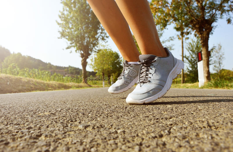 Running shoes jump. Fitness woman rotation feet hop run on asphalt road at sunset. stock photo