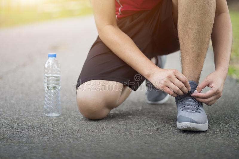 Running shoes - Man knee down with tie sneakers shoestring, Runner man getting ready for jogging at garden.  royalty free stock images