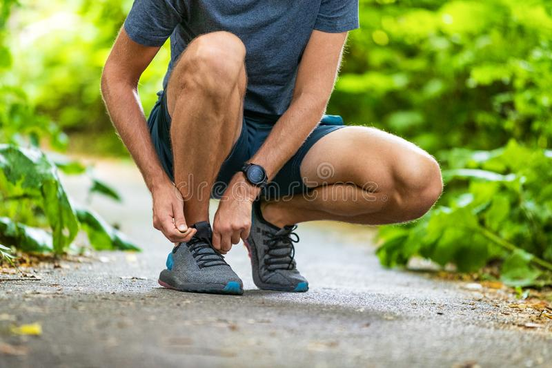 Running shoes sports smartwatch man tying shoe laces. Male fitness runner getting ready to jog in spring autumn jogging. Outdoor wearing technology wearable stock photos