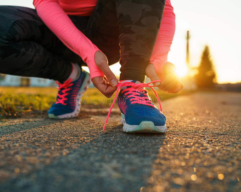 Running shoes - woman tying shoe laces stock photo