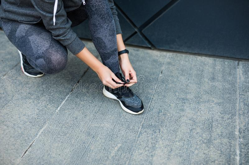 Running shoes - woman tying shoe laces. Closeup of female sport fitness runner getting ready for jogging outdoors in the city royalty free stock photo