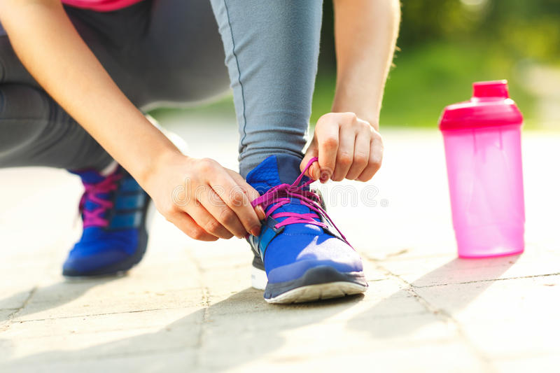 Running shoes - woman tying shoe laces stock images