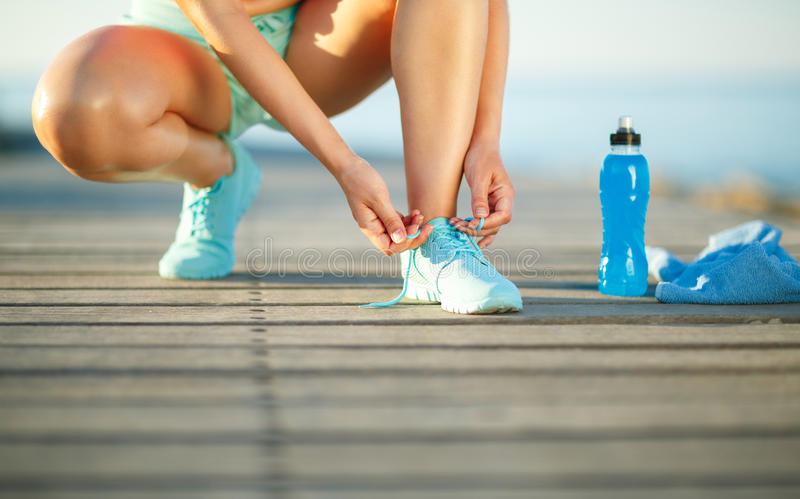Running shoes - woman tying shoe laces royalty free stock photos