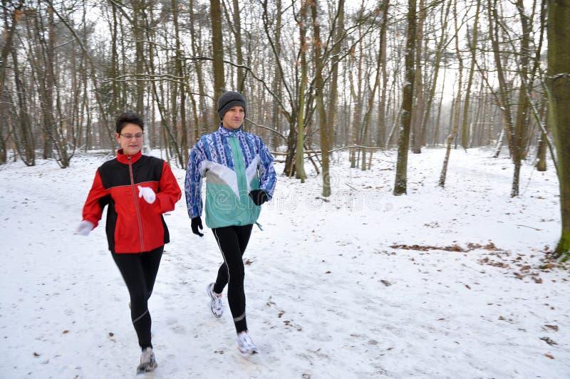 Running in the snow, sharp on men. Family running in the snow, sharp on men royalty free stock photos