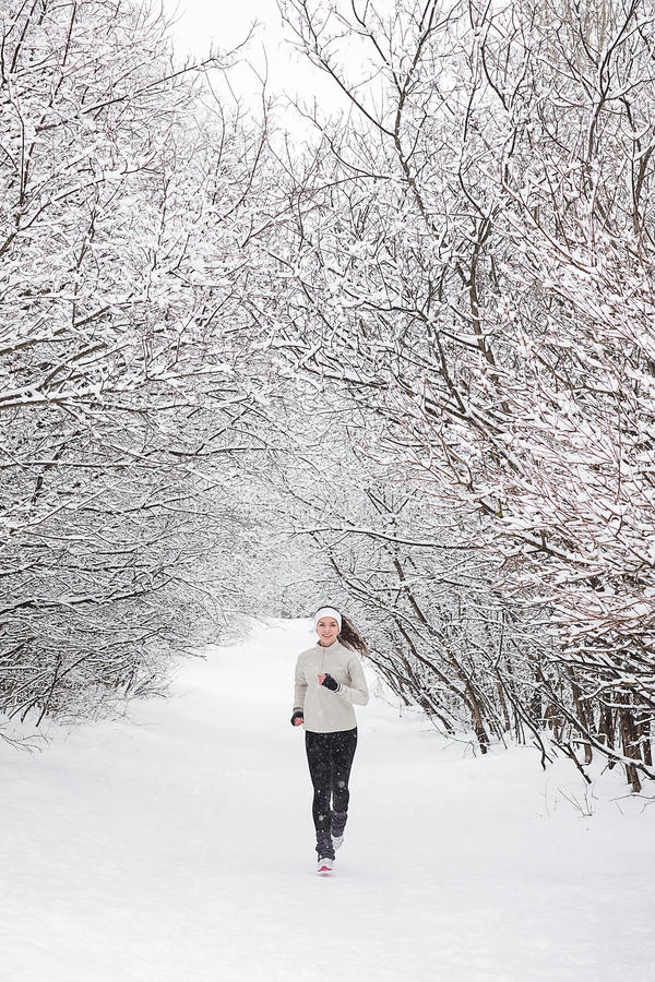 Running in the snow. Running in the woods in winter. Beautiful young woman running jogging in the winter forest. Trees in the snow. Weather snow cloud. Fitness royalty free stock images