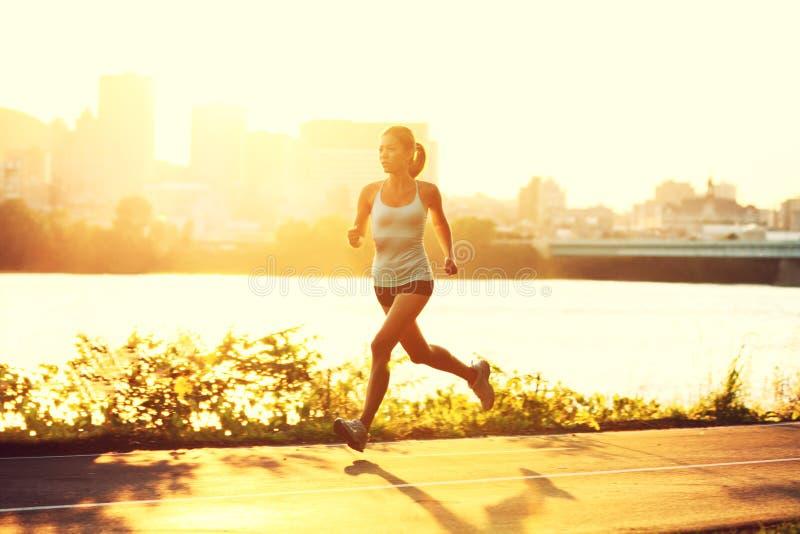 running solnedgång för kvinnliglöpare arkivfoto