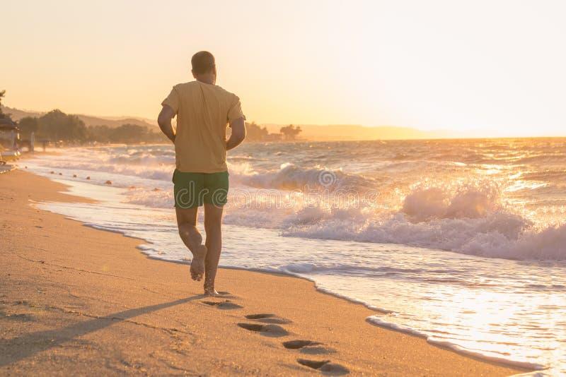 running solnedgång för strandman arkivfoto