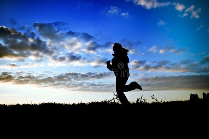 running solnedgångkvinna royaltyfri foto