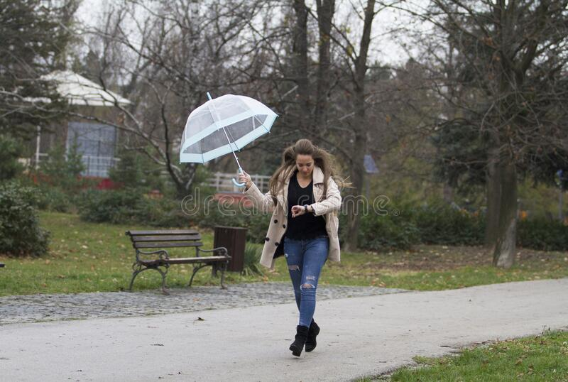 Running somewhere with an umbrella while looking at her watch. Young girl with long hair.Running somewhere with an umbrella while looking at her watch. Probably stock image