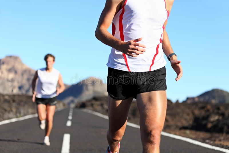 Running Sport. Runners on road in endurance run outdoors in beautiful landscape. closeup of man legs and torso with male runner in the background. Shallow DOF royalty free stock photography