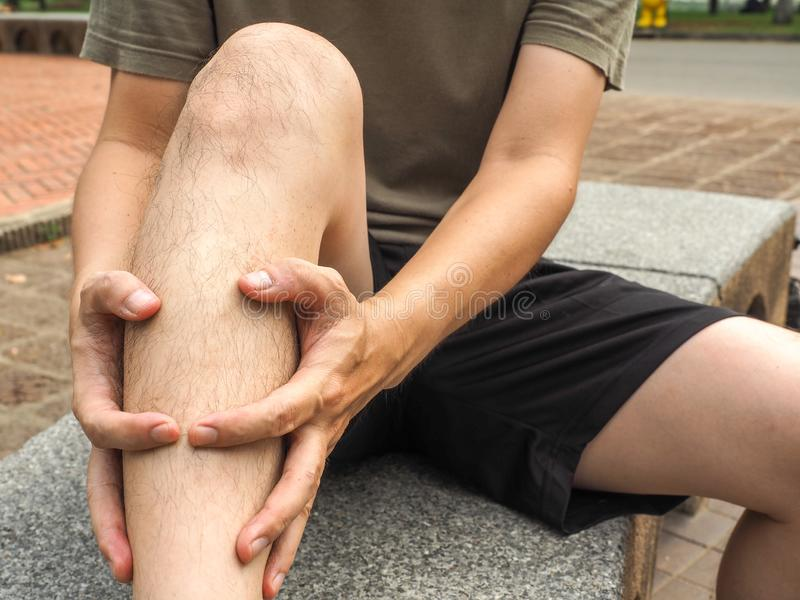 Running sport injury. male athlete jogger wearing man runner massaging calf muscle before workout.  stock photo