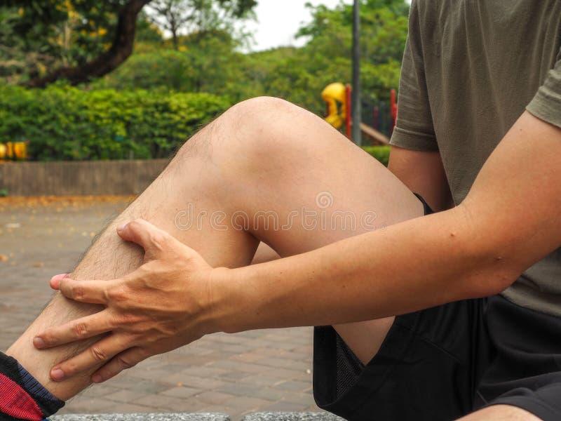 Running sport injury. male athlete jogger wearing man runner massaging calf muscle before workout.  royalty free stock photo
