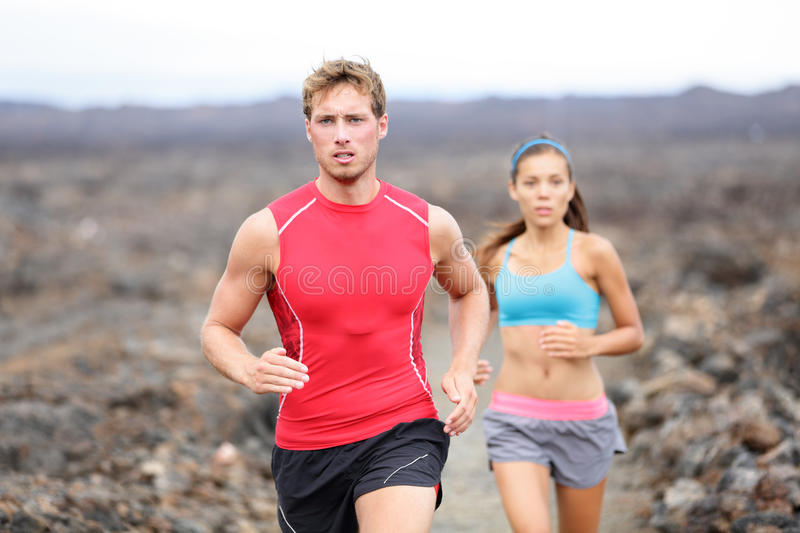 Running sport people running cross country trail. Running sport people jogging on trail in cross country run outdoors training for marathon or triathlon. Fit royalty free stock photo