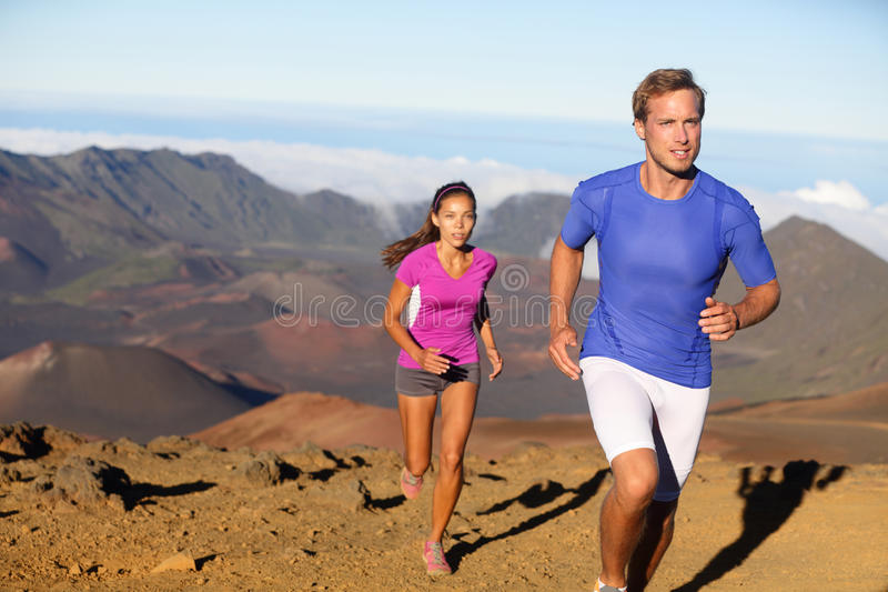 Running sport - trail runners in cross country run. Man and women couple athletes training in amazing nature landscape. Fit male fitness model and female royalty free stock photos