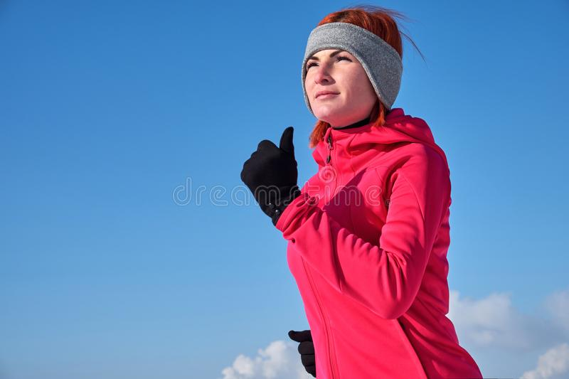 Running sport woman. Female runner jogging in cold winter forest wearing warm sporty running clothing and gloves royalty free stock images