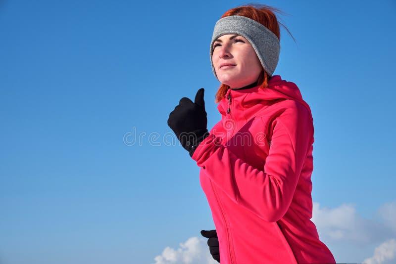 Running sportkvinna Kvinnliglöpare som rustar i den kalla vinterskogen som slitage varma sportiga running kläder och handskar royaltyfria bilder