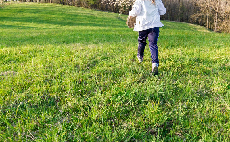 Running in spring. Carefree little girl running in the meadow in spring stock image