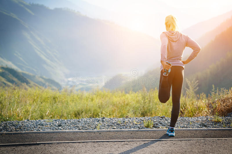 Running stretching. Athlete at the top of the mountain. stock photography