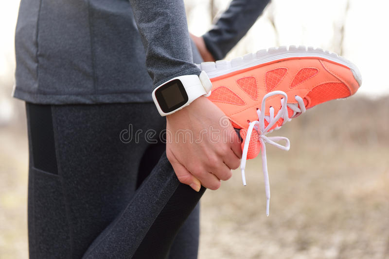 Running stretching - runner wearing smartwatch. Closeup of running shoes, woman stretching leg as warm-up before run with sport activity tracker watch at wrist stock images