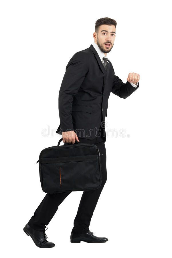 Running surprised business man carrying laptop case side view looking at camera royalty free stock image