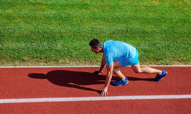 Running tips for beginners. Man athlete stand low start position stadium path. Runner ready to go. Joint mobility. Exercises to improve flexibility and function royalty free stock images