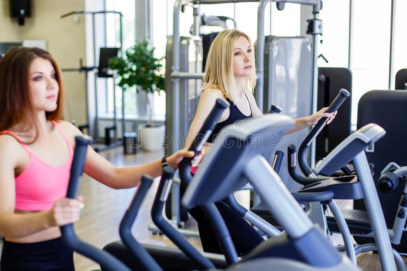 Running together. Side view close up of young beautiful women looking away while running on treadmill at gym. stock photo