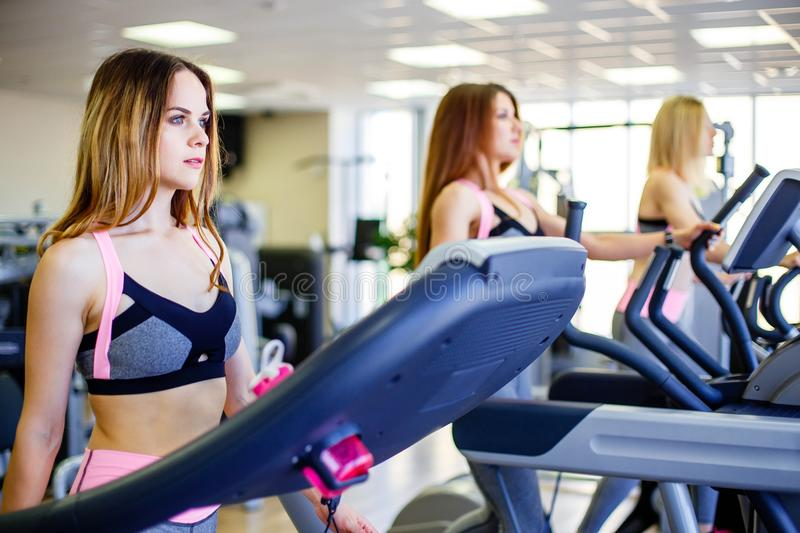 Running together. Side view close up of young beautiful women looking away while running on treadmill at gym. stock image