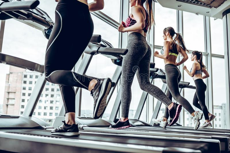 Side view of young beautiful women looking away while running on treadmill at gym. stock photos