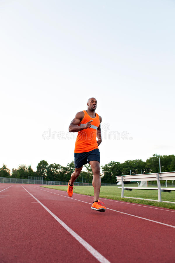 Running At the Track. African American man in his 30s running at a sports track outdoors stock images