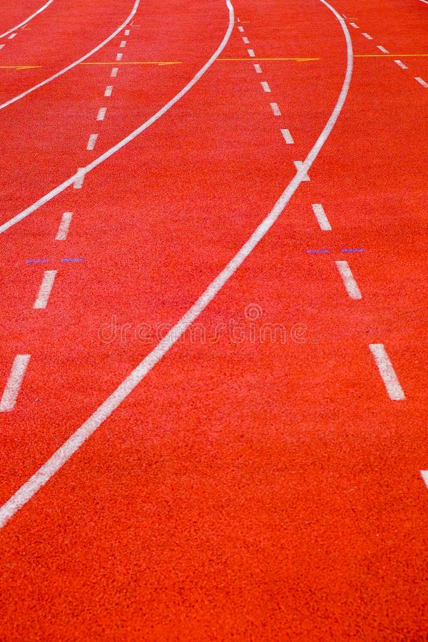 Running track with curve and dash lines. Close-up running track with curve and dash lines on brown field arena royalty free stock images