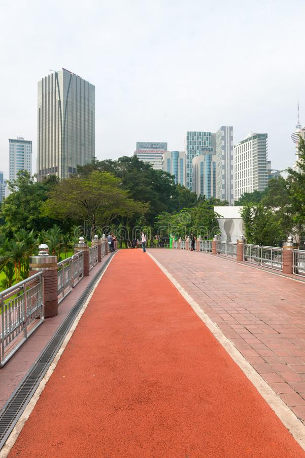 Running track in KLCC downtown city park with skyscappers on background. KUALA LUMPUR, MALAYSIA - OCT 2014: Running track in KLCC downtown city park with stock images