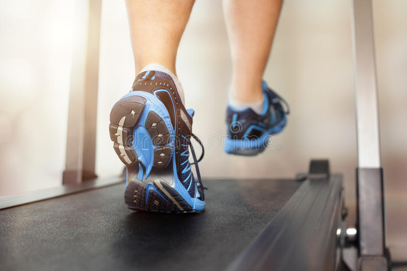 Running on treadmill. Man running in a gym on a treadmill concept for exercising, fitness and healthy lifestyle royalty free stock photos