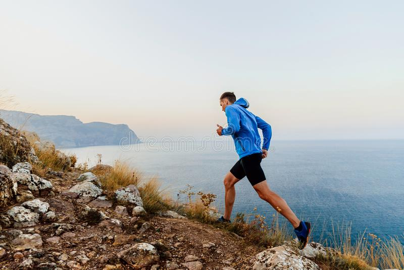Running uphill in trail male athlete runner. On sea background royalty free stock images