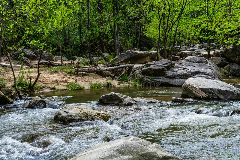 Running Water In The Woods. White water rapids erode boulders in a forest in a state park royalty free stock photos
