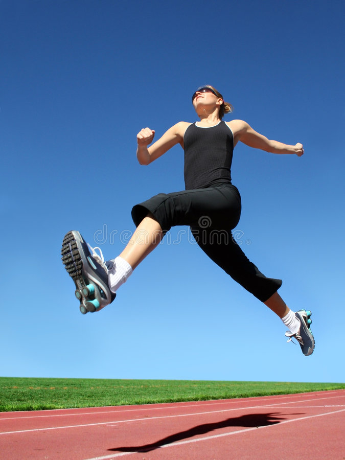 Running woman. Yong woman running on a racetrack royalty free stock images