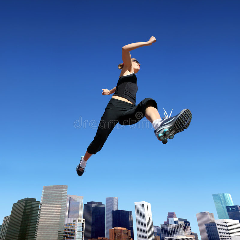 Running woman. A young blond woman jumping high above downtown stock photos