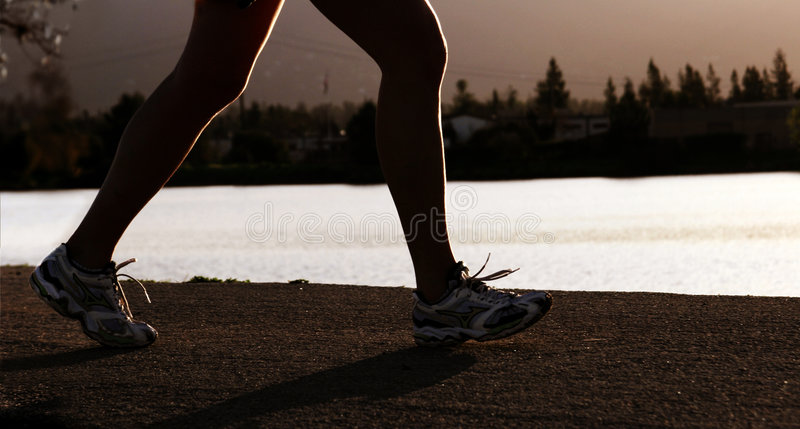 Running Woman. Woman jogging along a river at sunset stock photos