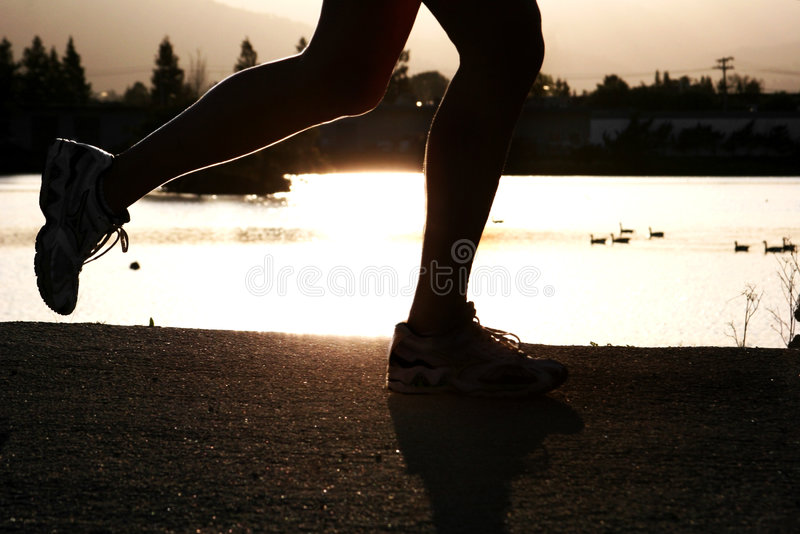 Running Woman. Woman jogging along a river at sunset royalty free stock photos