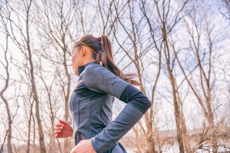 Running woman in autumn forest outdoors in morning fresh air doing cardio workout exercise living a healthy lifestyle. Girl runner royalty free stock photography