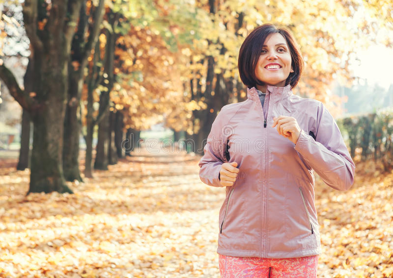 Running woman in the autumnal park royalty free stock image