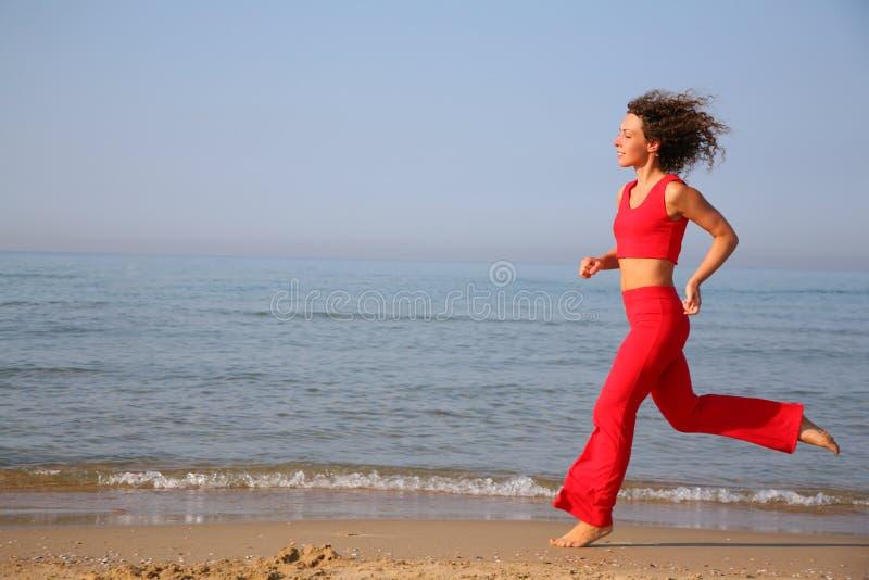 Running woman on beach stock photo