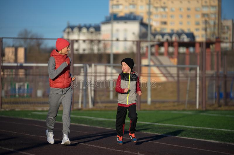 Running woman and boy. Runners jogging running track. Family fitness model training outside stock images