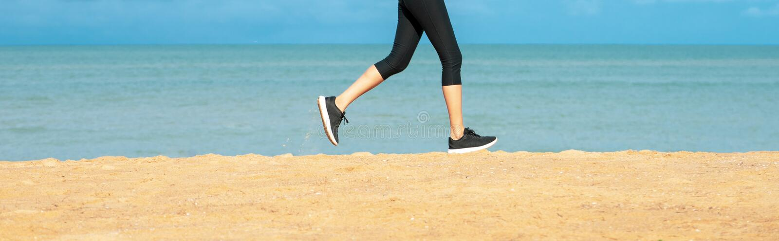 Running woman. Female runner jogging during outdoor workout on beach. Fitness model outdoors. Feet of young woman jogging on the b royalty free stock photo