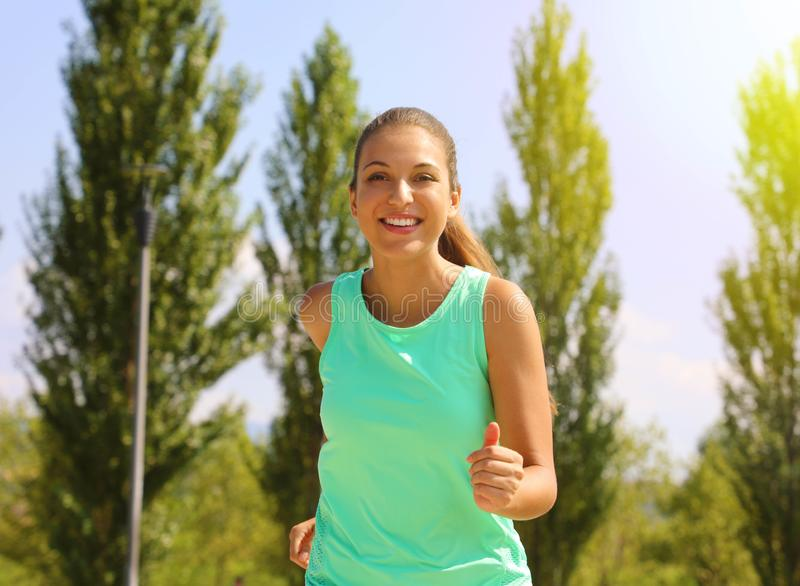 Running woman. Female runner jogging during outdoor workout in the park. Beautiful fit fitness model outdoors royalty free stock photos
