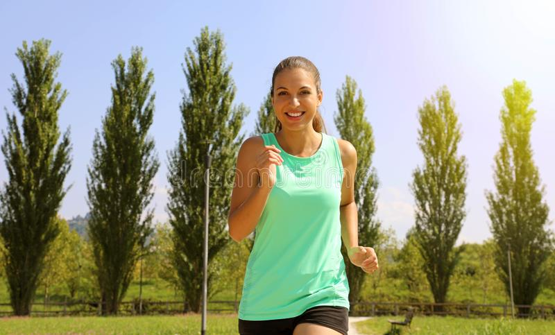 Running woman. Female runner jogging during outdoor workout in the park. Beautiful fit fitness model outdoors royalty free stock photography