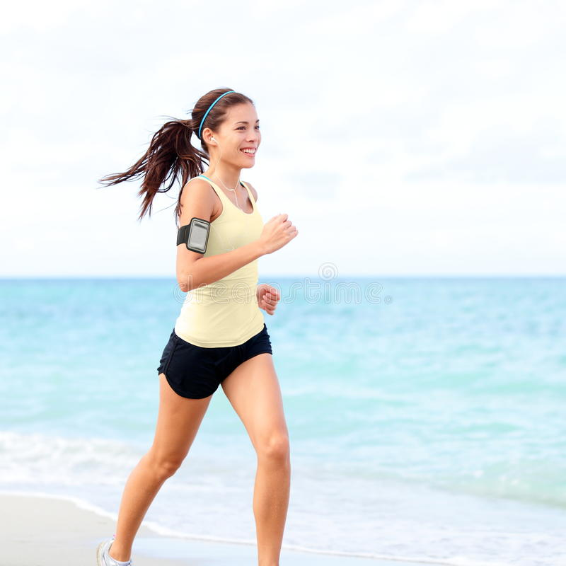Running woman jogging on beach listening to music. In earphones from smart phone mp3 player smartphone armband, Female runner training for marathon on beautiful royalty free stock images