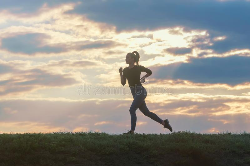 Running woman morning workout. Female Runner. Jogging during sunrise. Workout in a Park. Sporty young woman. Fitness model stock image