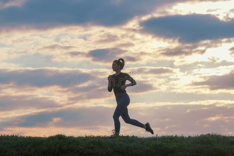 Running woman morning workout. Female Runner. Jogging during sunrise. Workout in a Park. Sporty young woman. Fitness model royalty free stock photos