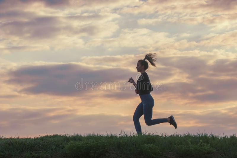 Running woman morning workout. Female Runner. Jogging during sunrise. Workout in a Park. Sporty young woman. Fitness model stock photo