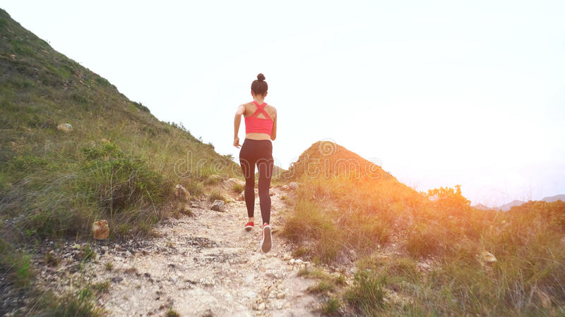 Running woman on mountain road. Sport girl exercising outside in mountains royalty free stock images